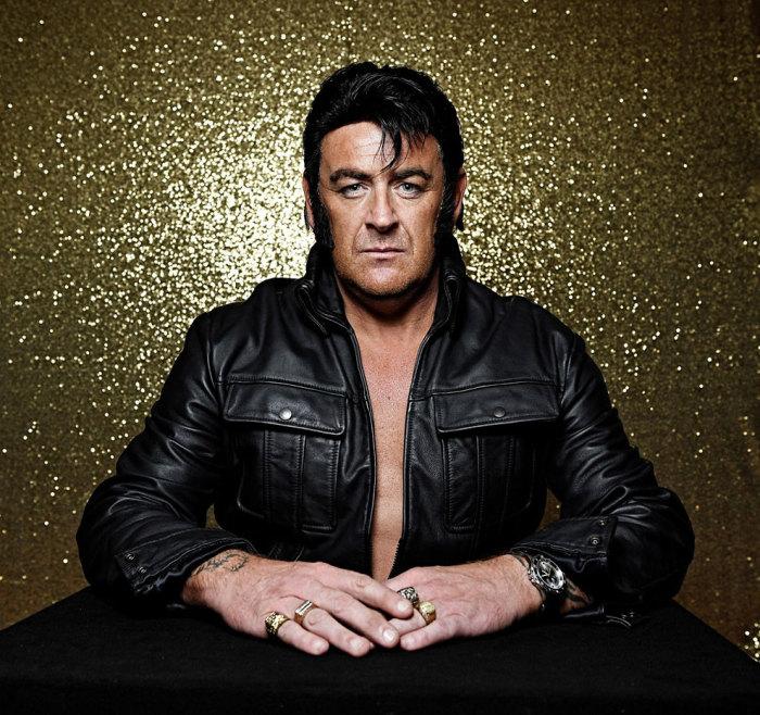 Мужчина в черной кожаной куртке и печатками на золотистом фоне.