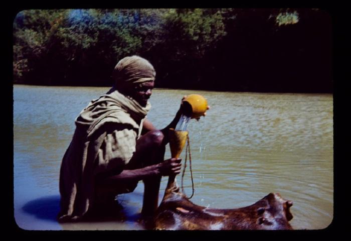 Африканец наливает воду в дубленую шкуру, которая выполняет роль сосуда для воды.