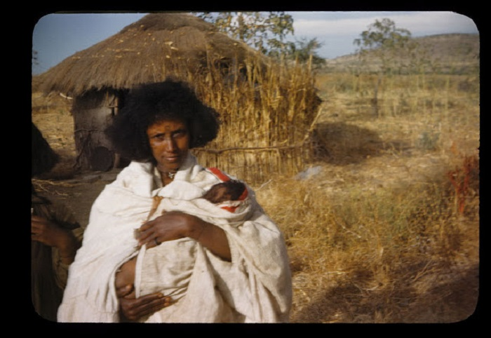 Женщина в белых одеяниях с ребенком на руках после родов.