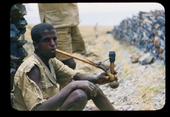Африканец отдыхает в тенечке под забором, выкуривая трубку.