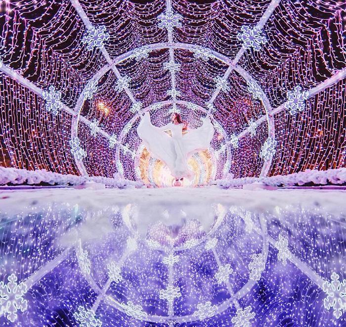 На фоне невероятной световой инсталляции, выполненной с виде сияющего тоннеля с огромными снежинками, модель фотографа выглядит сказочной феей.