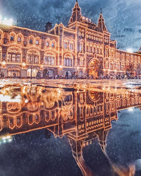 Отражение здания, щедро украшенного праздничными огнями, выглядит совершенным и сказочным.