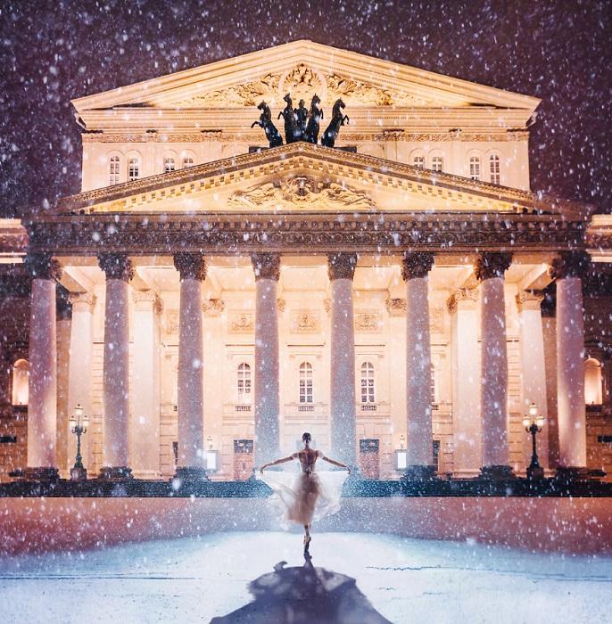Хрупкая фигурка балерины застыла под падающим снегом перед освещенной громадой театра оперы и балета.