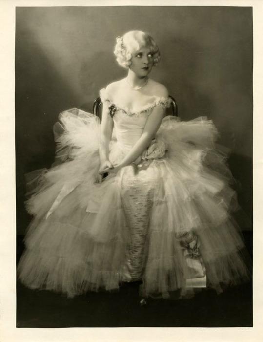 Актриса в платье из тюлевой ткани и атласа, украшенное вышивкой.