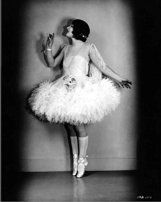 Артистка в юбке-пачке, украшенной белоснежными перьями.