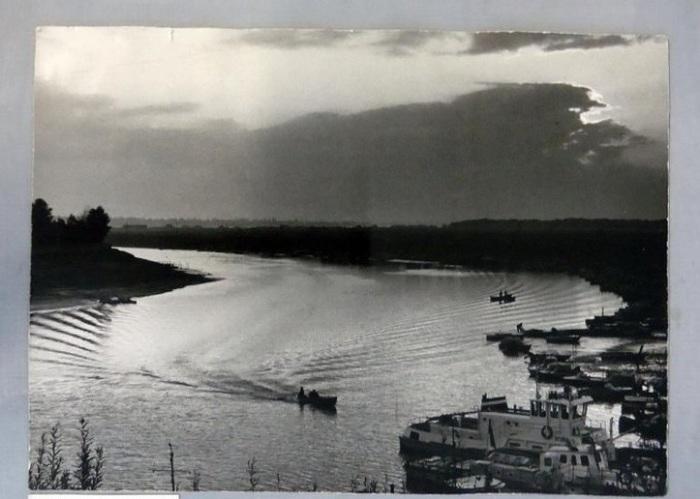 Рыбацкие лодки, возвращающиеся к причалу по тихим водам вечерней реки.
