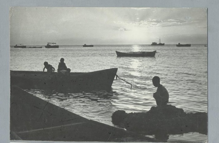 Ребятишки, играющие в лодке, которая пришвартована у каменистого берега Аральского моря.