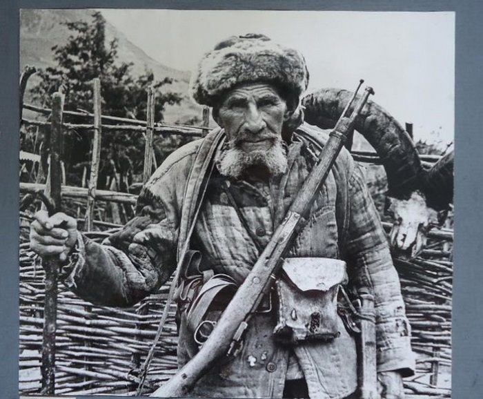 Пожилой осетинский охотник в полной экипировке с внушительным трофеем на заднем плане.