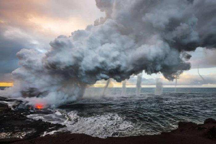 Выливающаяся в море огненная лава создает огромные шлейфы пара, порождая несколько вихрей.