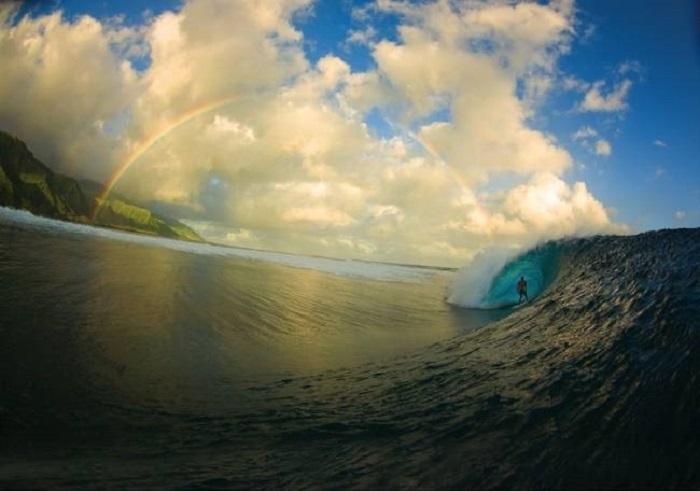 Серфер внутри волны на фоне радуги.