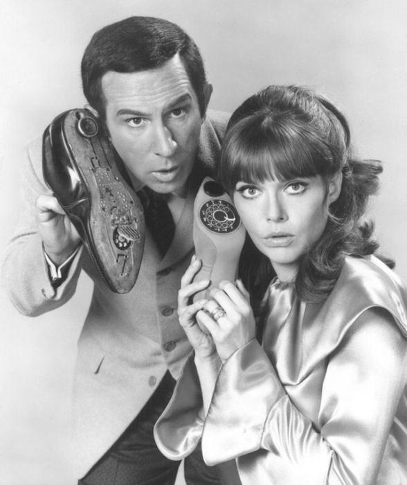 Молодая пара, изображающая шпионов с портативными телефонами того времени.