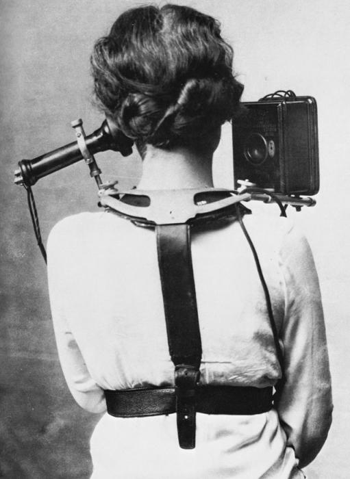 Женщина с телефоном, который зафиксирован специальными ремнями на спине.