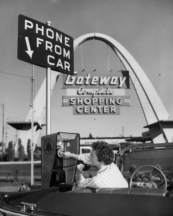 Автомобилистка звонит с телефона - автомата, не выходя из автомобиля.