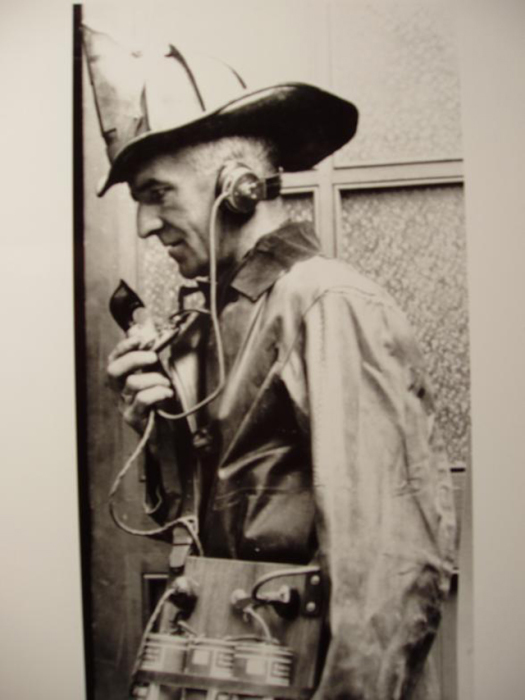 Пожарный принимает вызов по телефону.
