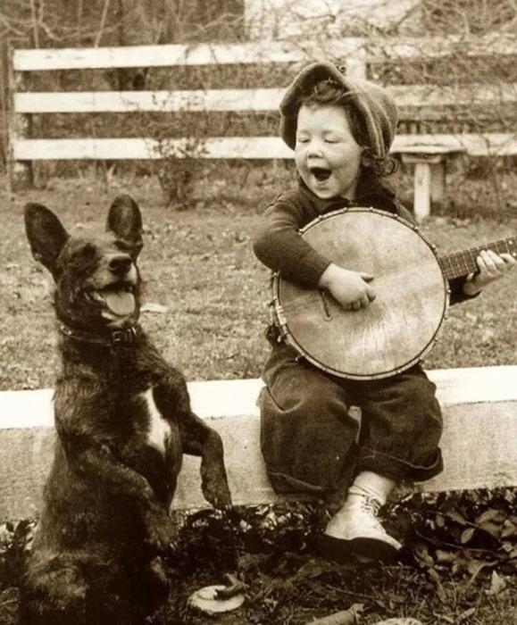 Девочка играет для своей собаки.