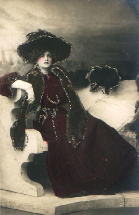 Женщина в насыщенном бордовом платье с тёмными аксессуарами.