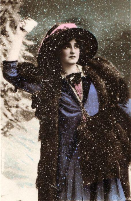 Чудесная танцовщица, певица и актриса в превосходном синем наряде радуется снегу.