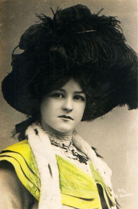 Серьезная дама с хорошим вкусом в чёрной шляпе и ярким жёлтым воротником.