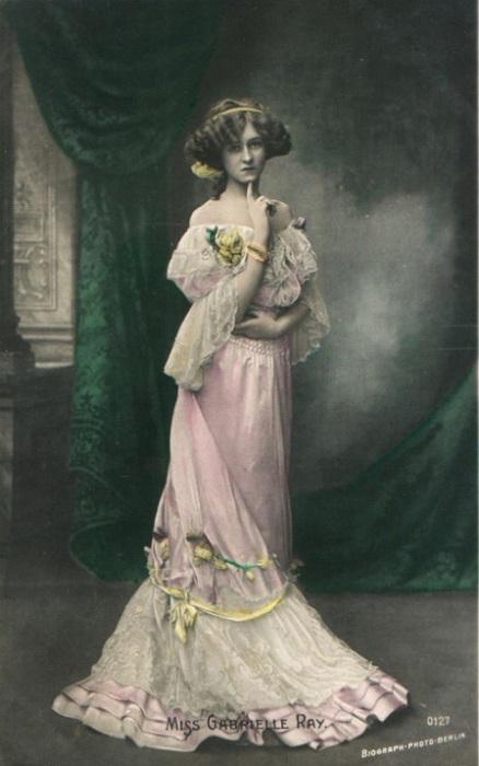 Красивая дама в белоснежном платье, разбавленном жёлтыми украшениями с солнечной лентой на причёске.