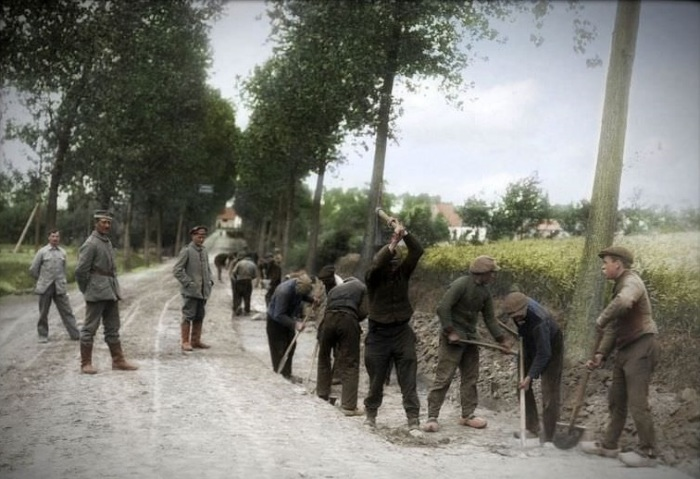 Немецкие солдаты надзирают за ходом выполнения ремонта дороги бельгийскими пленными.