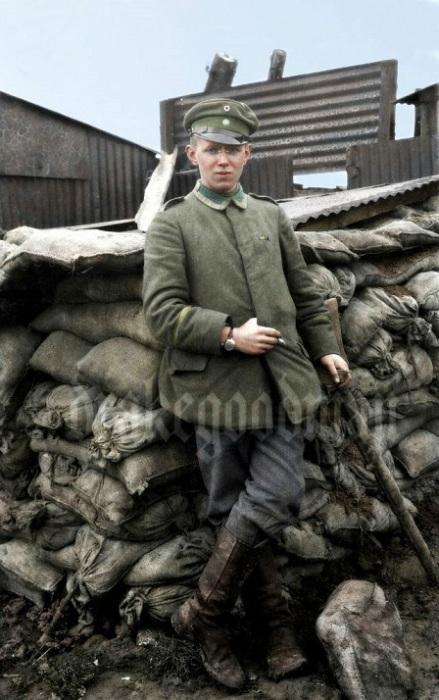 Молодой сержант позирует у возведенного укрепсооружения.