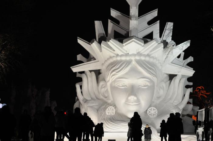 Посетители внимательно рассматривают и фотографируются у снежной скульптуры.