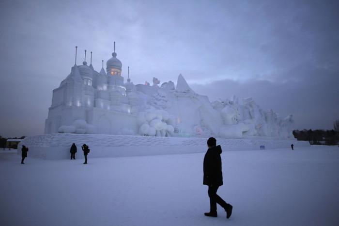 Посетители рассматривают ледяную скульптуру.