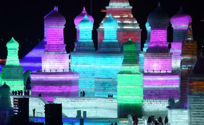 Посетители прогуливаются по замку из ледяных блоков.