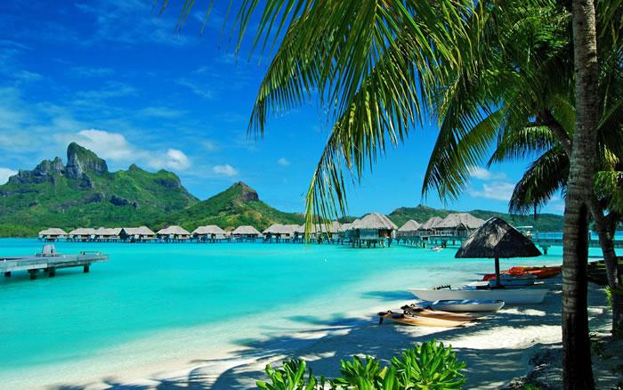 Курортный отель Four Seasons Bora Bora с видом на потрясающие бирюзовые воды и частный пляж располагает роскошными бунгало на воде и прибрежными виллами с видом на гору Отеману.