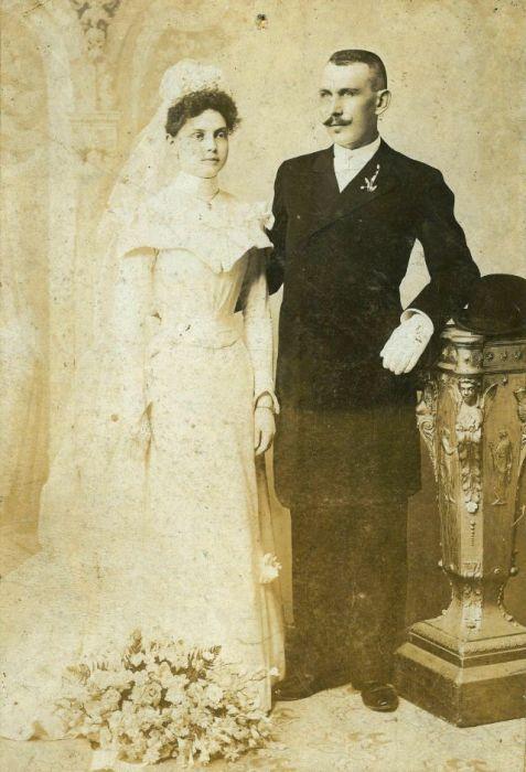 Невеста в закрытом свадебном платье с длинными рукавами.