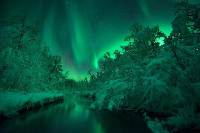 Северное полярное сияние в небе над рекой Ломаас. Фотограф Arild Heitmann.