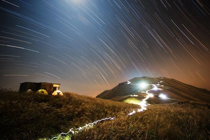 Над горой в Гонконге и на еще более дальнем расстоянии звезды как будто горят в ночном небе, оставляя за собой следы, но на самом деле они изображают движение Земли вокруг своей оси. Фотограф Chap Him Wong.