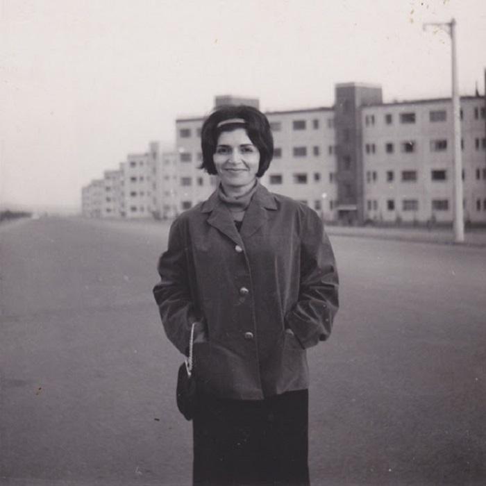 Молодая девушка у первой в Иране массовой застройки жилыми зданиями.