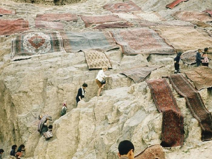 Американцы в качестве туристов у скал с постиранными коврами.