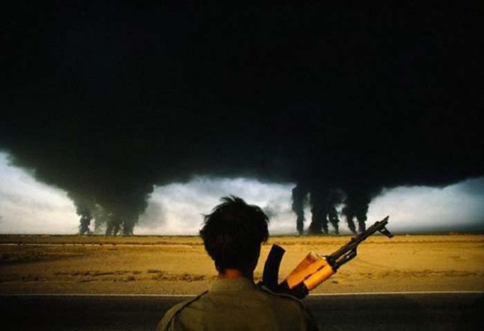 Иранские войска наблюдают, как горят нефтяные месторождения, подожжённые иракскими войсками во время войны в Персидском заливе. (1990).