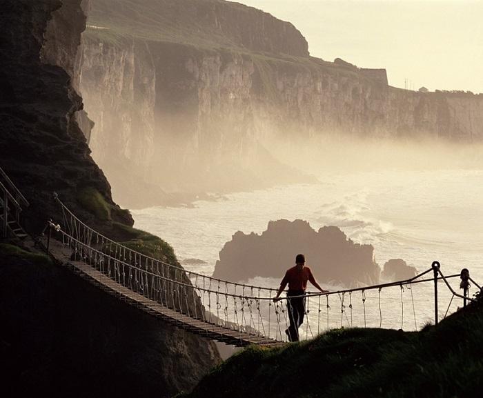 Веревочный подвесной мост Каррик-а-Ред имеет длину 20 метров и на 30 метров возвышается над скалами около графства Баллинтой в Северной Ирландии. Фотограф: Christopher Hill.