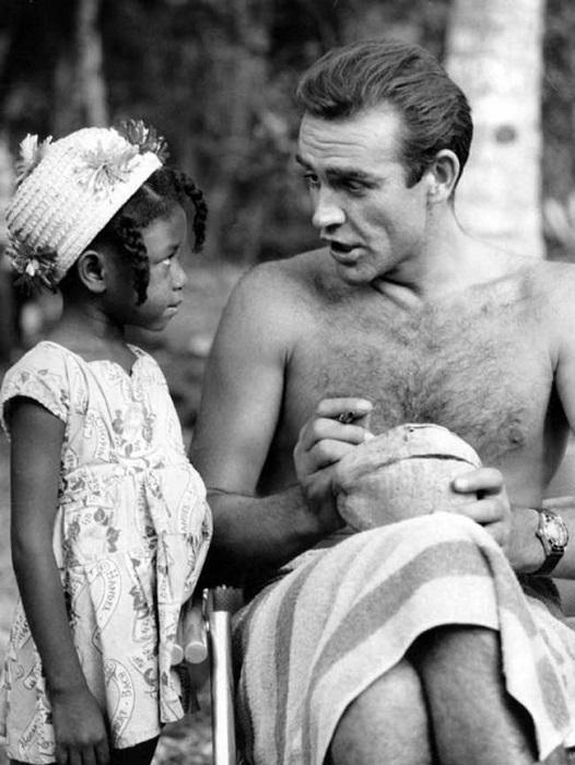 """Шон Коннери подписывает кокос для маленькой фанатки из Ямайки на съемках фильма """"Доктор Ноу"""". 1962 год."""
