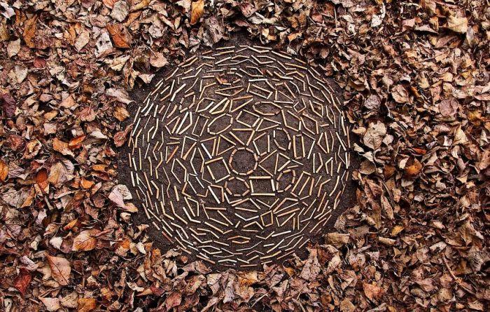 Объемный арт-объект, созданный из палочек на расчищенной от опавших листьев земле.