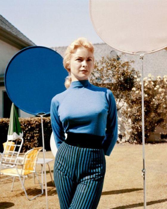 Женщина в брюках с завышенной талией в полоску и синей кофте.