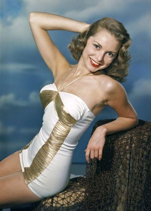 Молодая девушка в бело-золотом платье присела отдохнуть под голубым небом.