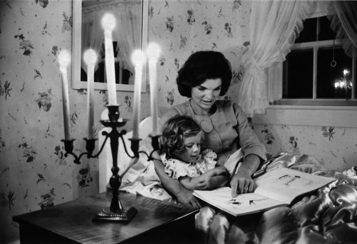 Джеки Кеннеди читает книгу дочери Кэролайн в летнем загородном доме.
