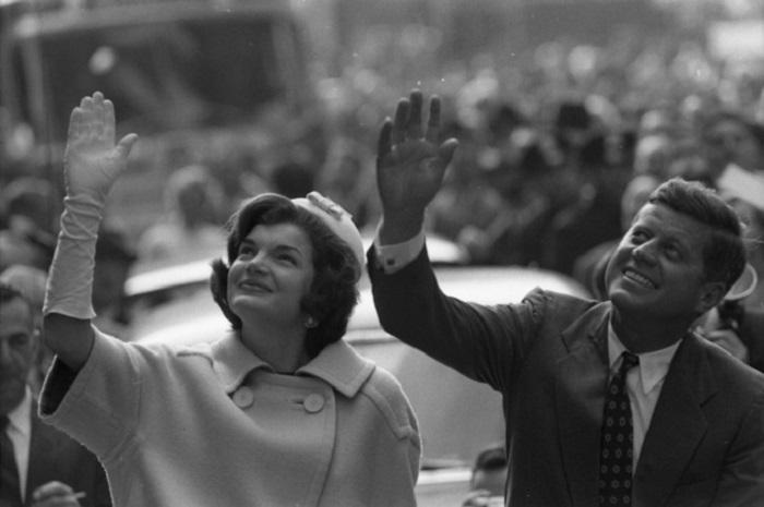 Чета Кеннеди приветствует избирателей из открытого кабриолета.