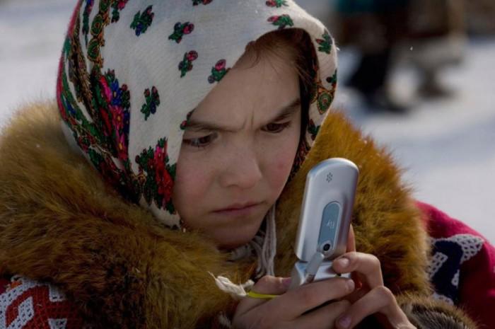 Коренная жительница разбирается в настройках мобильного телефона.