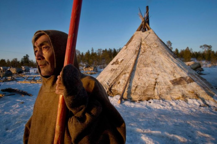 Ненецкий пастух Александр Тергачев перед своим чумом, покрытым оленьими шкурами.