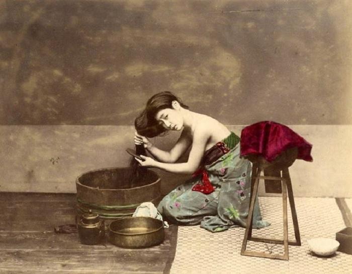 Женщина втирает специальные масла в волосы.