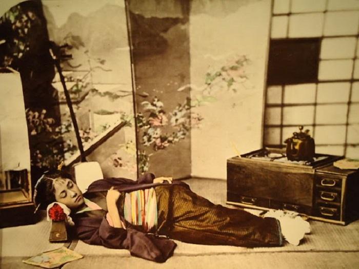 Девушка спит на циновке.