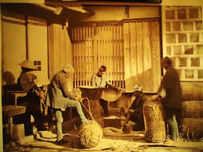 На ферме рабочие закатывают рисовые тюки.