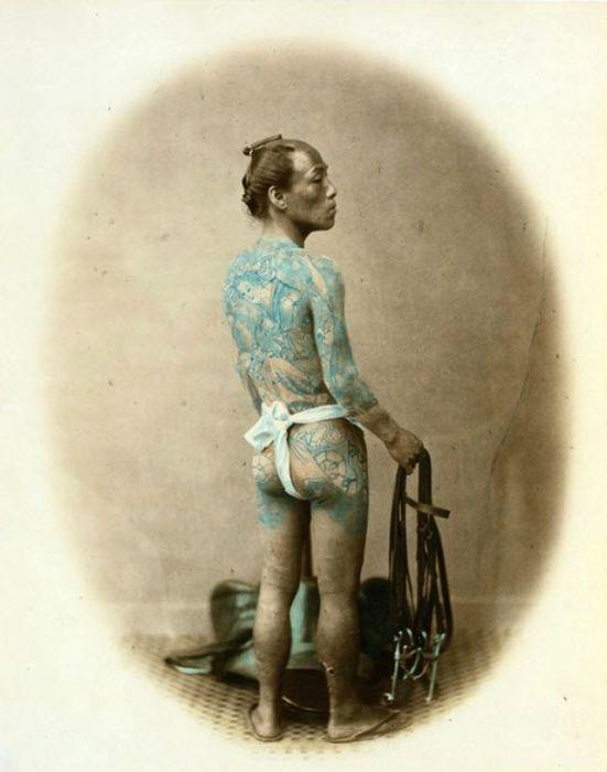 Мужчина с татуировками в правой руке держит уздечку, а на полу лежит возле него седло.