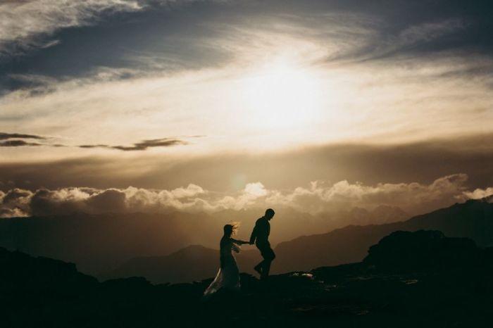 Молодожены в лучах заходящего солнца взбираются на вершину горы. Автор фотографии: неизвестен.