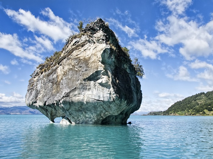 Яркие синие пещеры, частично погруженные в бирюзовые воды озера Каррера.
